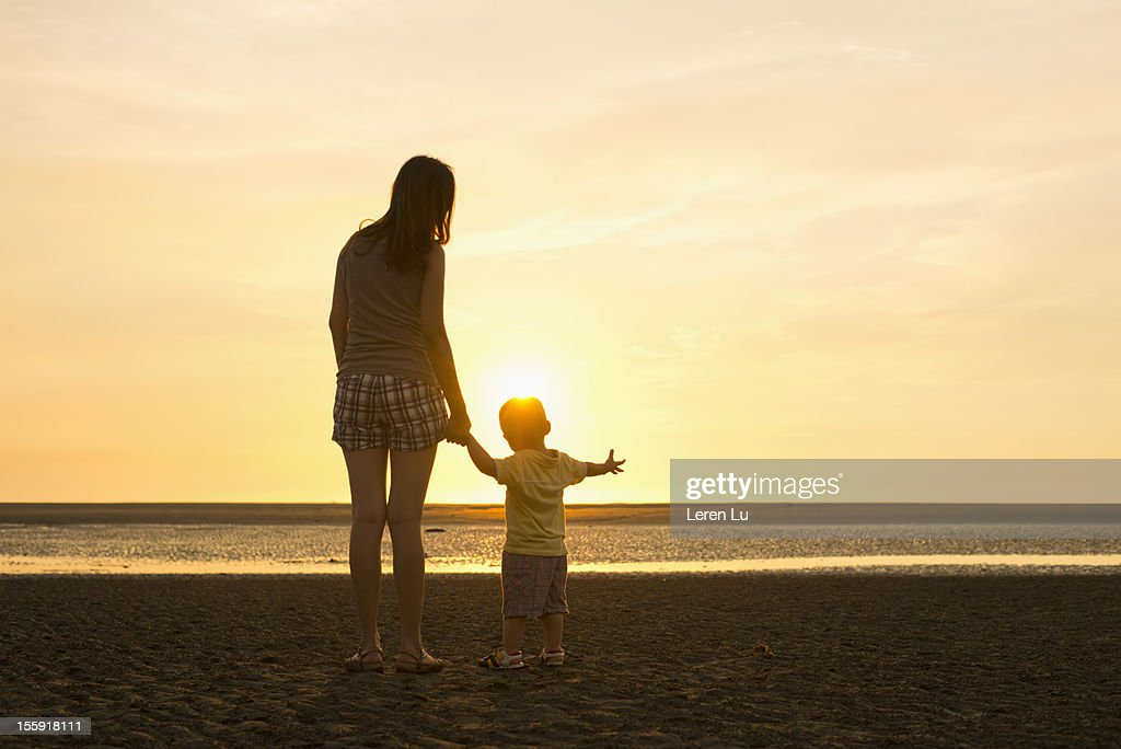 Mother and child stand on beach at sunset : Stock Photo
