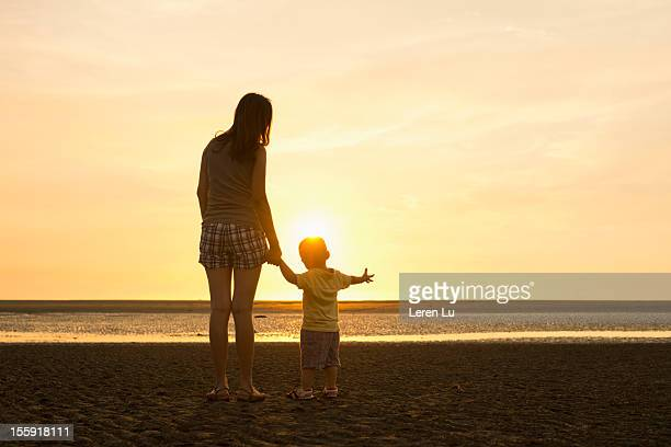 Mother and child stand on beach at sunset