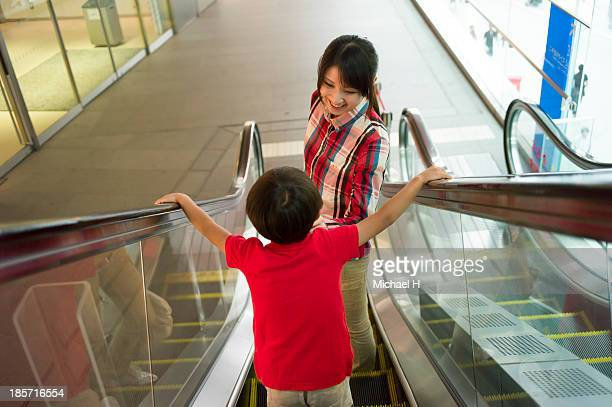 mother and child standing on moving escalator