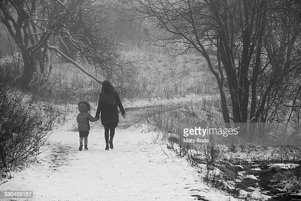 Mother and child strolling in the forrest park