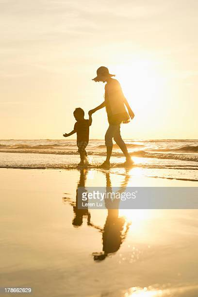 Mother and child walking on the beach