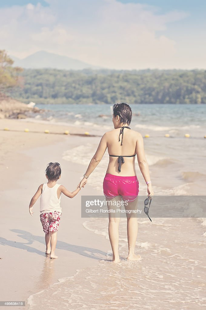 Mother and child walking on the beach : Stock Photo