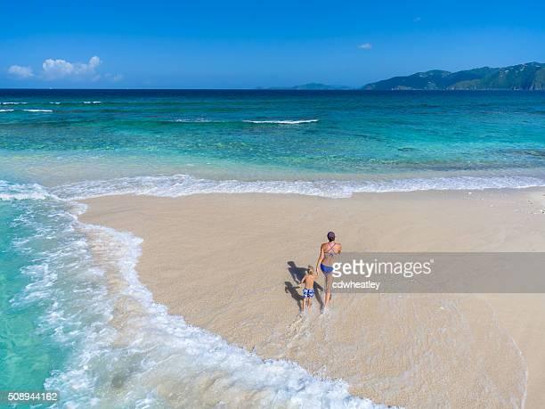 母と子のトロピカルビーチを歩く