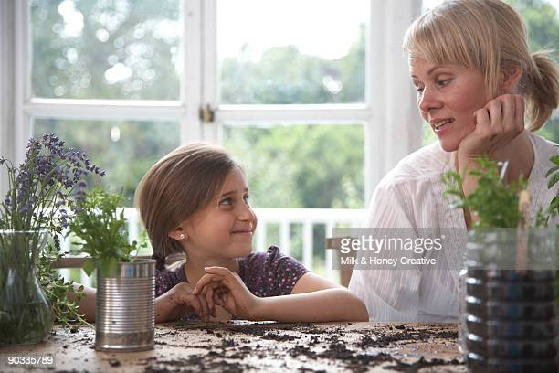 Mother and child with plants in recycled pots