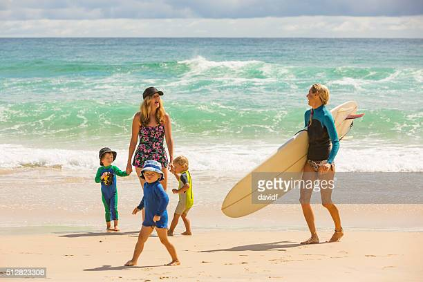 Mother and Children at the Beach With Female Surfer