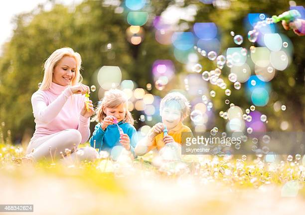 Mother and children blowing bubbles in the park.