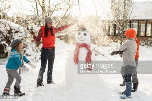 Mother And Children Building Snowman In Garden : Foto de stock