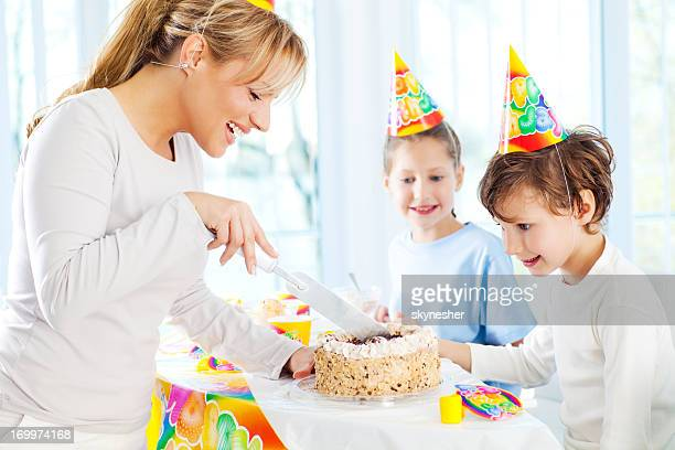 Mother and children cutting the birthday cake.