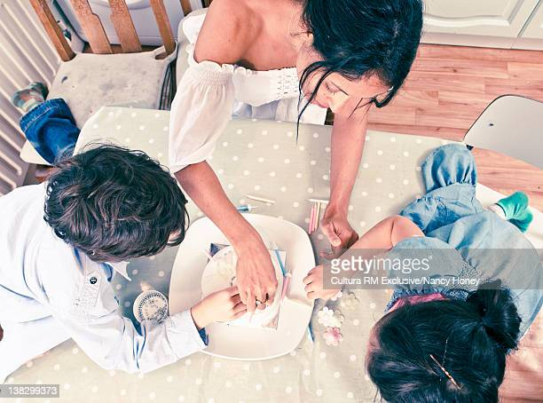 Mother and children decorating cake
