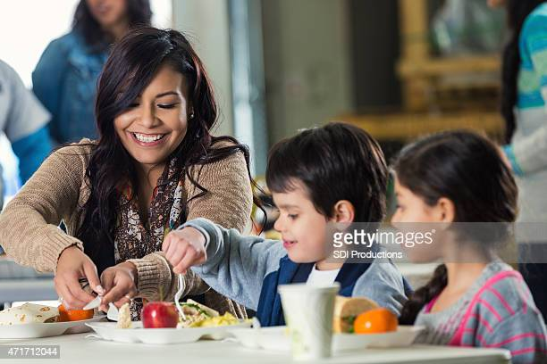 Mother and children eating meal in food bank soup kitchen