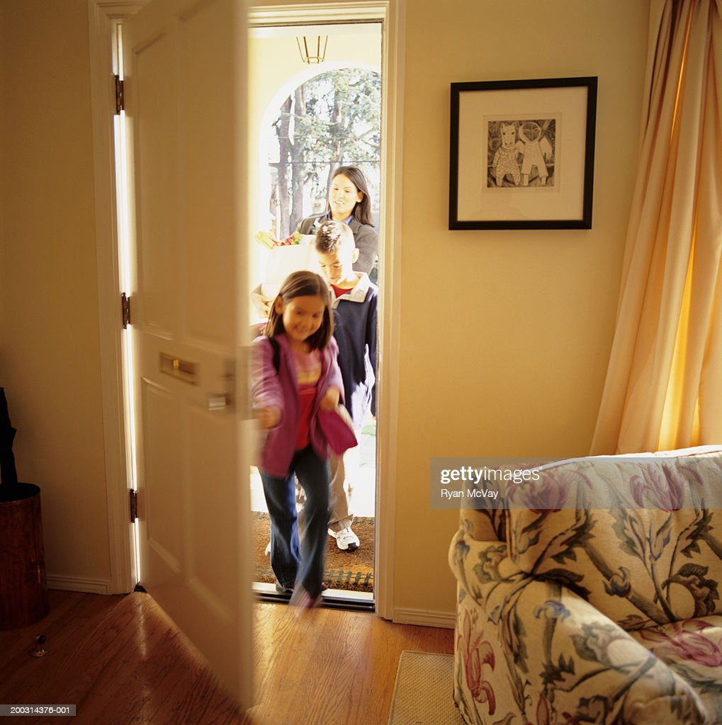 Mother and children (6-7), (8-9), entering house