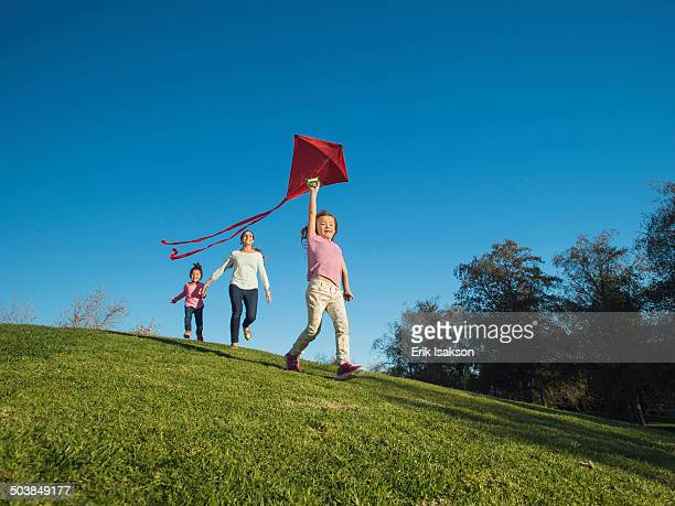 Mother and children flying kite in park