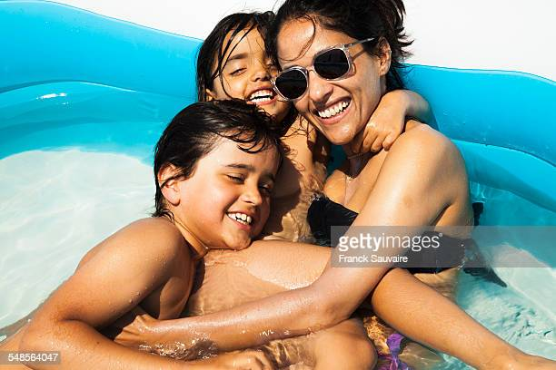 Mother and children fooling around in paddling pool