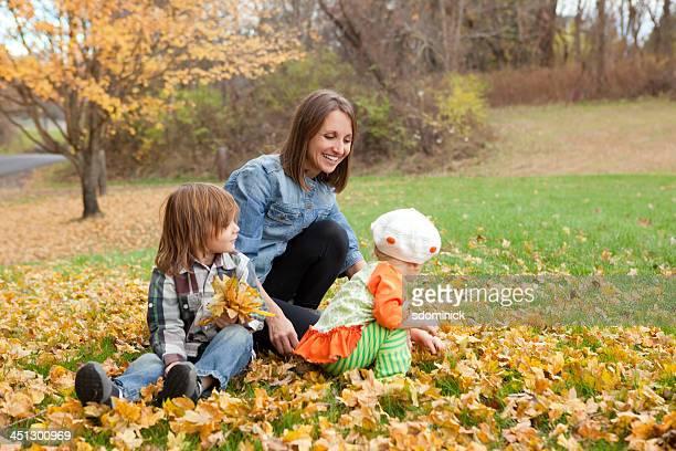 Mutter und Kinder treffen Herbst Blätter