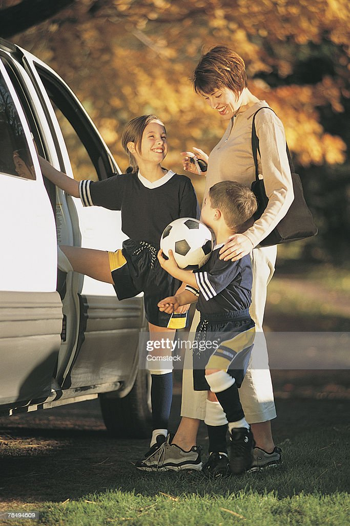 Mother and children getting in van after soccer game