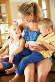 Mother And Children Having Breakfast Sitting On Kitchen Counter