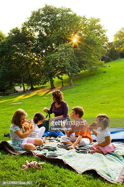 Mother and children (4-9) having picnic in park