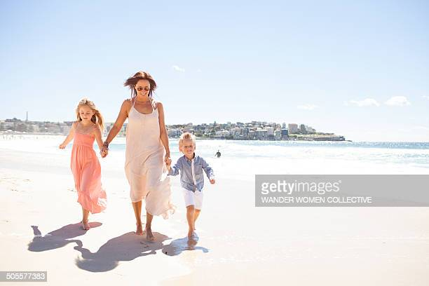 Mother and children holding hands along beach