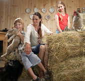 Mother and children in farm kitchen with animals