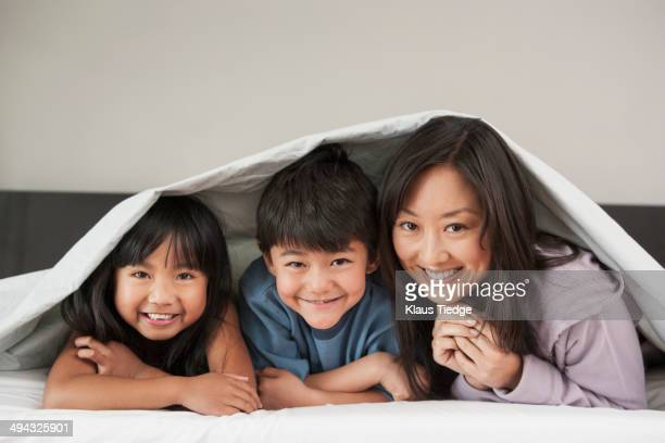 Mother and children laying under bed covers