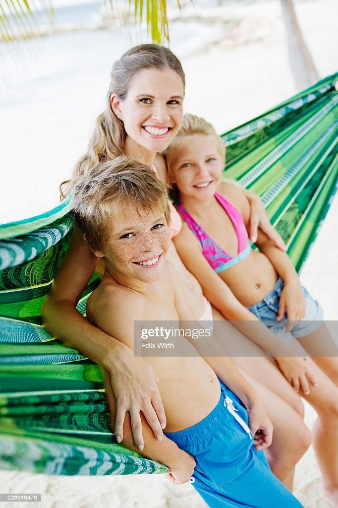 Mother and children (10-12) leaning against hammock on beach : Stock Photo