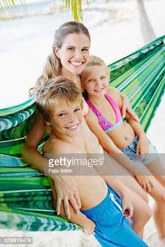 Mother and children (10-12) leaning against hammock on beach : Foto stock