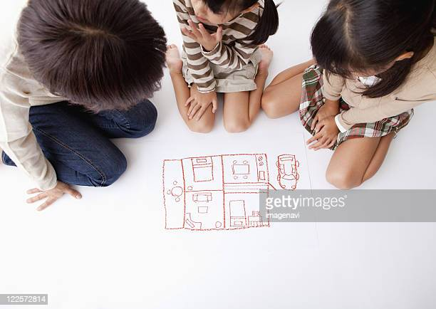 Mother and children looking at a pictuere of room layout
