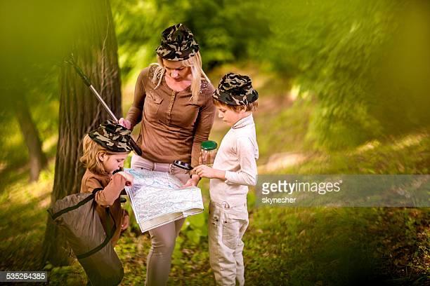 Mutter und Kinder, die auf der Karte im Wald.