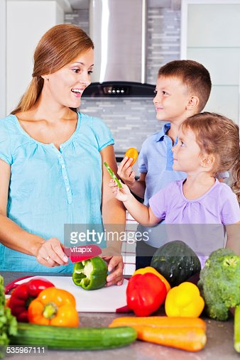 Mother and children making healthy dinner in the kitchen : Stock Photo