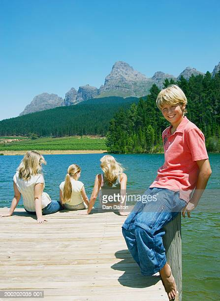 Mother and children (8-14) on jetty, portrait of boy on wooden stump