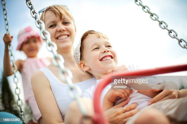 Mother and children on swing