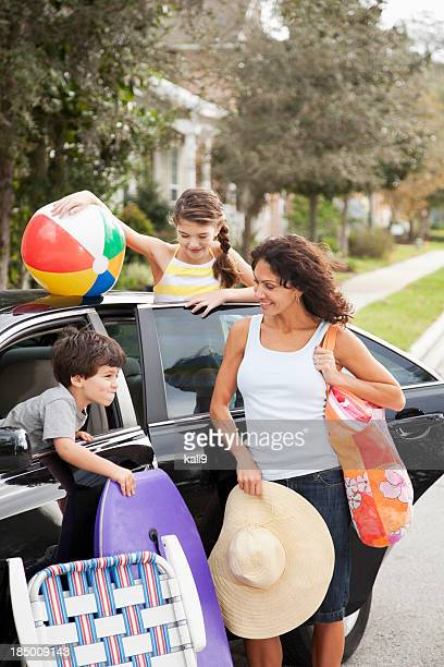 Mother and children packing car for trip to beach