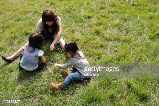 Mother and Children Playing on Grass : Stock Photo