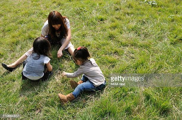 Mother and Children Playing on Grass