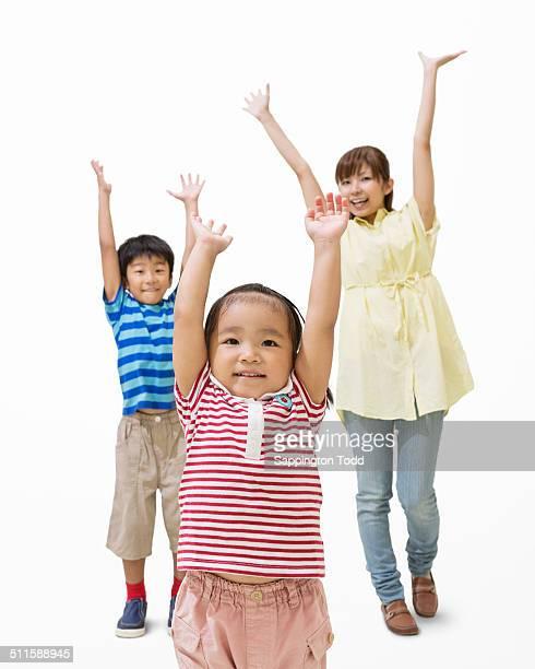 Mother And Children Raising Hands