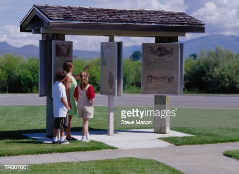Mother and Children Reading Tourist Information : Stock Photo