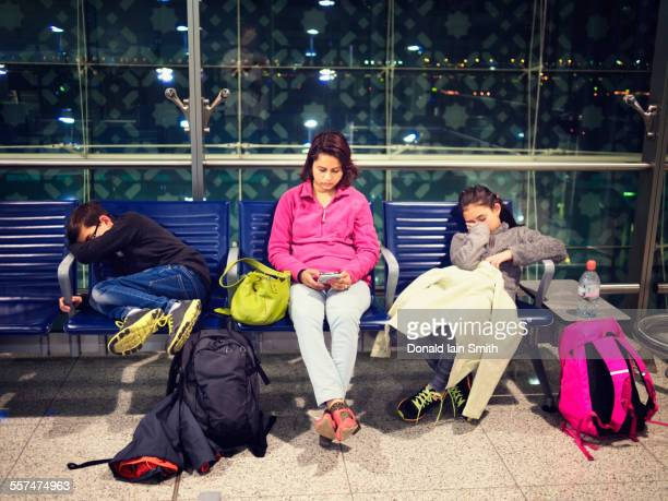 Mother and children relaxing in airport waiting area