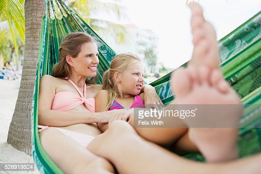 Mother and children (10-12) relaxing in hammock on beach : Stock Photo