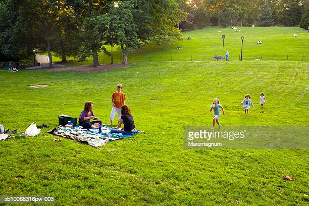 Mother and children (4-9) relaxing in park