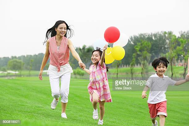 Mother and children running on grass