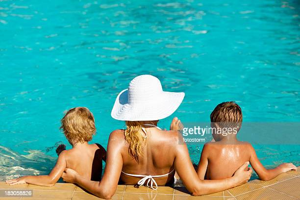 Mother and children sitting in the swimming pool