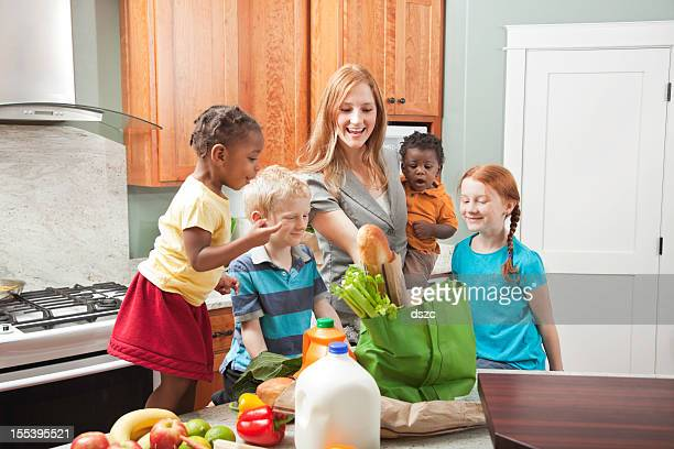 mother and children unbagging groceries in kitchen