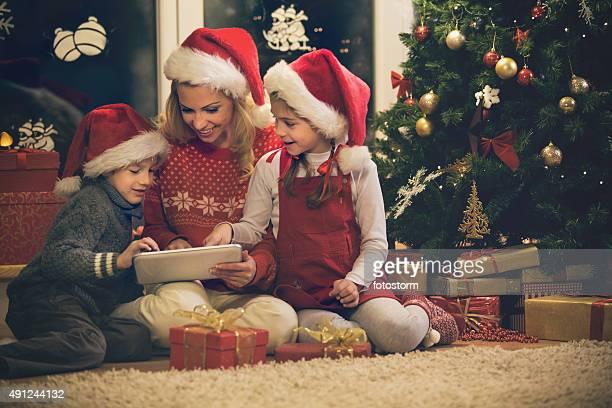 Mutter und Kinder, die mit digitalen tablet in der Nähe von Weihnachtsbaum