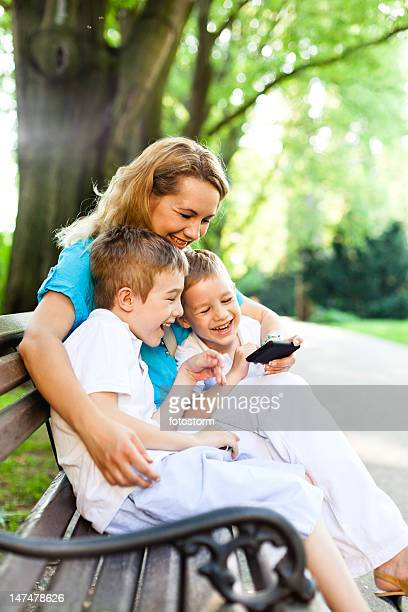 Mother and children using mobile phone in the park