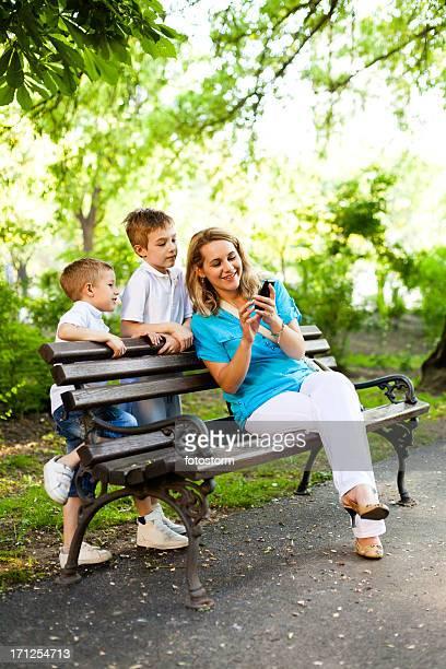 Mutter und Kinder, die mit Handy im park