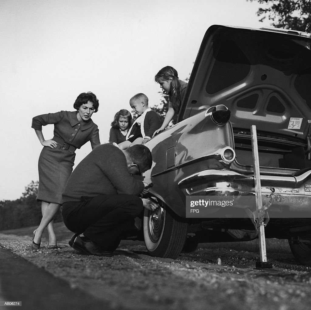 Mother and children (3-8) watching father change flat tire (B&W) : Stock Photo
