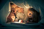 A woman and two children are reading in bed under a sheet.  The woman is holding a small black flashlight.  The little boy is near the mother.  Next to him, the little girl is holding her finger on th