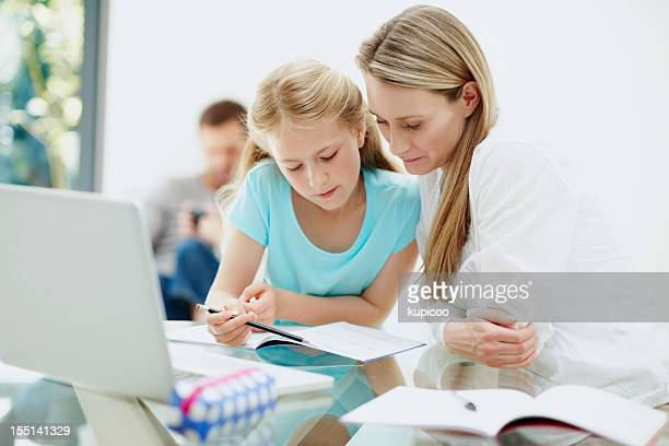 Mother and cute daughter studying with family in background