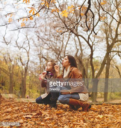 Mother and cute girl blowing bubbles