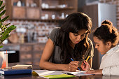 Mother and cute little daughter sitting at table and doing homework together at home, homework help concept